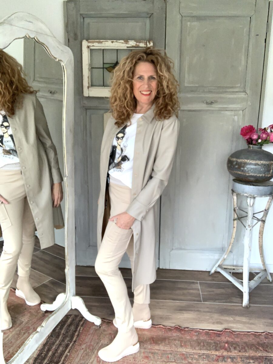 beige jogging broek met zijzakken t-shirt met print coco Chanel vegan leder lange jas Your Personal shopper